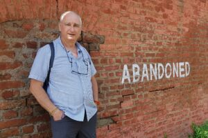 Vince Cullen standing outside an derelict building where the word 'ABANDONED' has been painted on the wall.